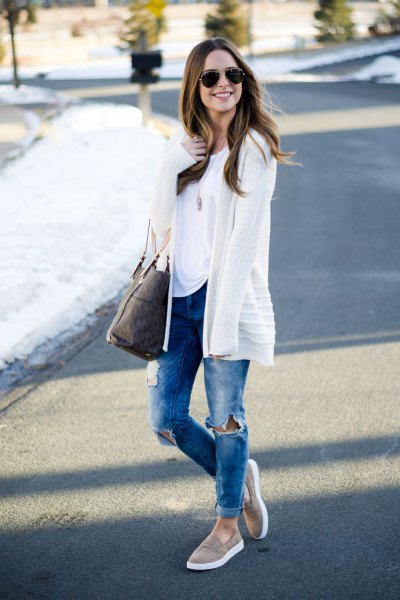 white cardigan with blue ripped jeans with cuffs and gray slip on hiking boots
