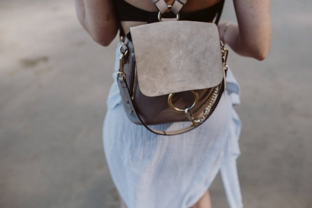 Airy mini dress made of white chiffon with a gray suede backpack handbag