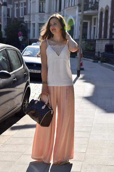 sleeveless top made of white chiffon and blushing trousers with wide legs