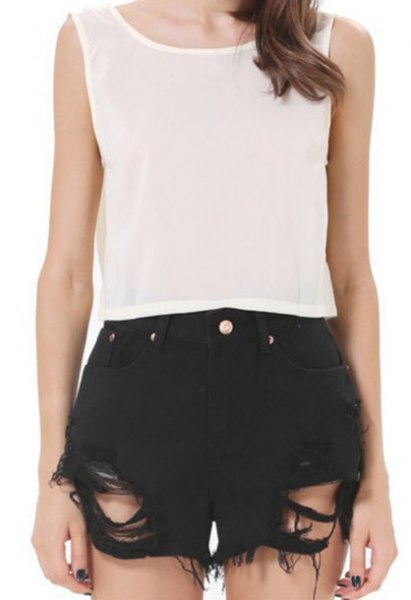 sleeveless top made of white chiffon, black shorts with rips