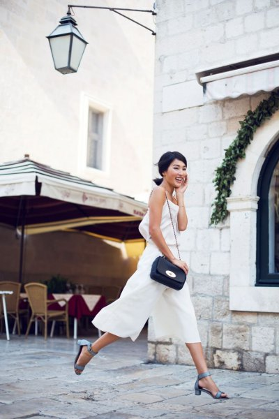 sleeveless top made of white chiffon with matching trousers with wide legs and gray heels