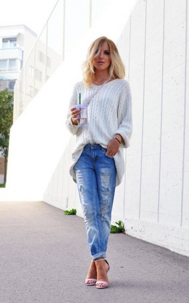 white, grainy knitted sweater with blue ripped jeans with cuffs