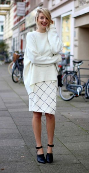 white, coarsely knitted sweater with round neckline and checked, knee-length skirt
