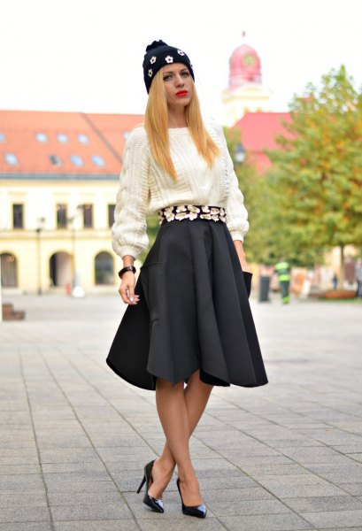 white, coarsely knitted sweater with black pleated skirt and heels