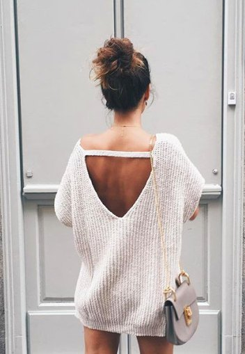 white chunky oversized sweater with an open back and mini shorts