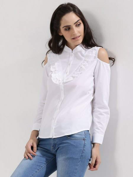 white shirt with ruffles on the front and light blue skinny jeans