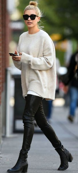 white, thick sweater with a round neckline and black leather pants