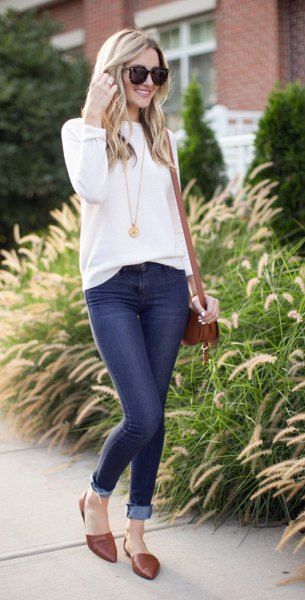 white sweater with a round neckline and dark blue skinny jeans with cuffs