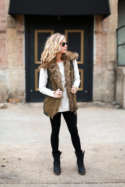 White crew neck sweater and olive green military vest made of faux fur