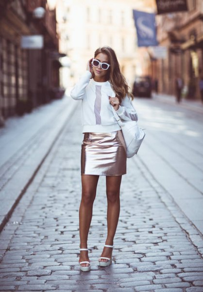 white sweatshirt with round neckline and rose gold-colored, figure-hugging mini skirt