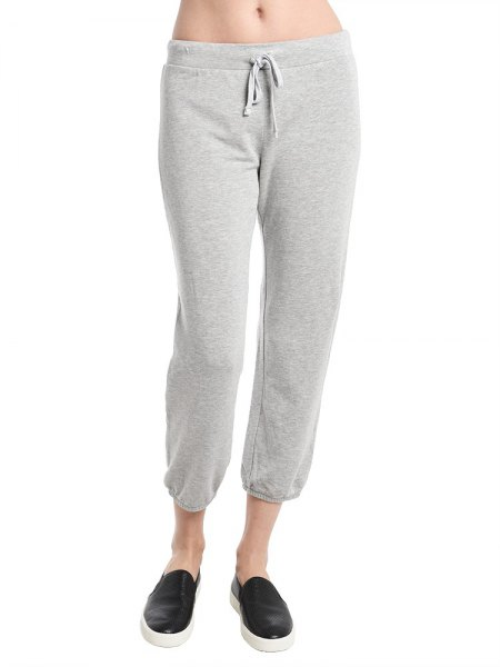 white crop top with light gray fleece pants and low sneakers