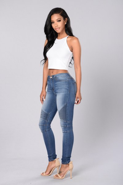 white, short halter top with blue-washed skinny moto jeans