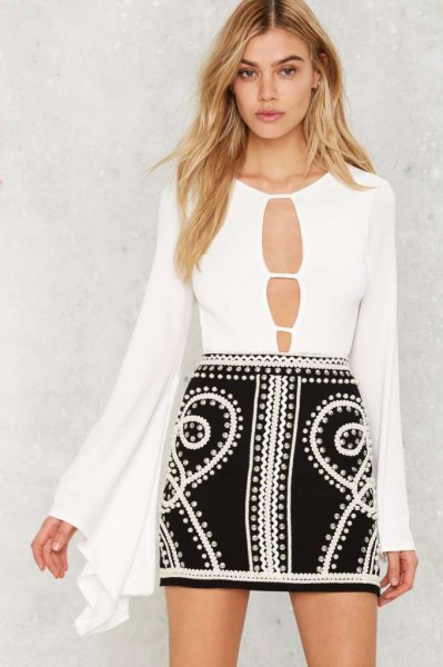 white bodysuit blouse with bell sleeves in front and black mini skirt