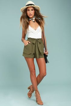 white camisole with a deep V-neckline and green shorts with a high tie front