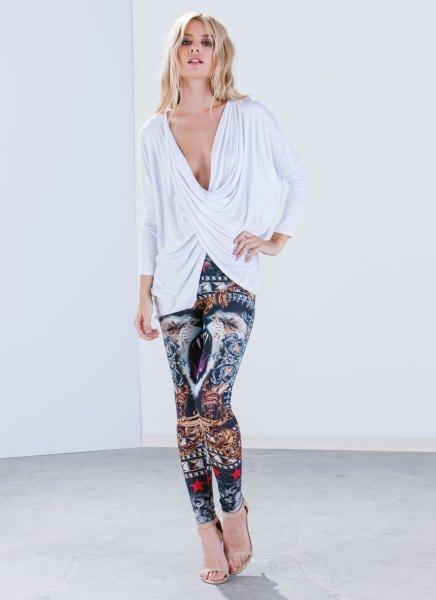 white, deep-sleeved, long-sleeved top with a V-neckline and leggings with tribal print