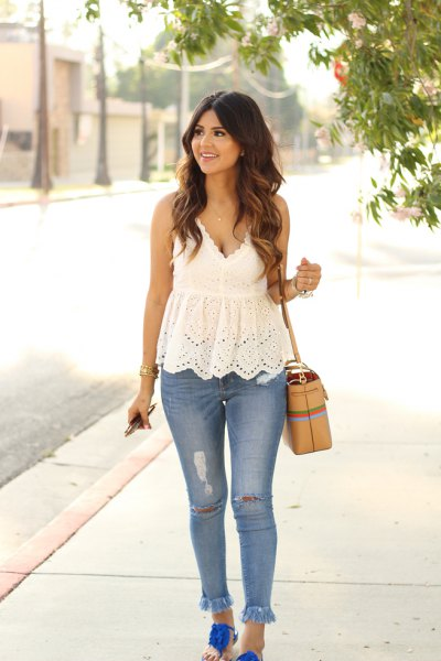 white peplum lace top with deep V-neckline and light blue jeans with fringed hem