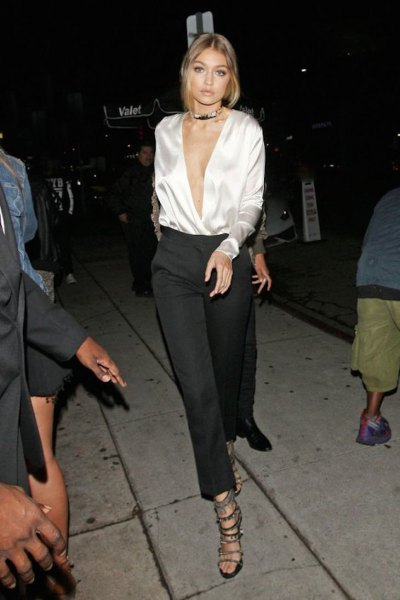 white silk blouse with deep V-neck and black, cropped trousers with wide legs