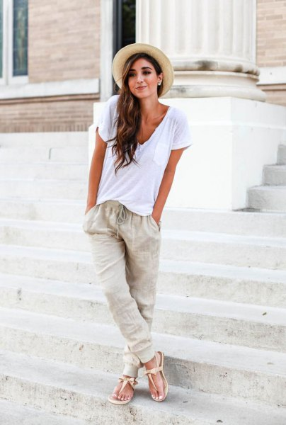 white t-shirt with deep V-neckline, straw hat and jogger linen pants