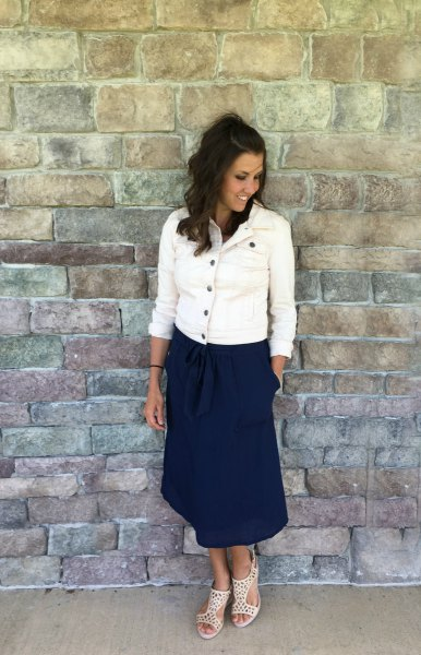 white denim jacket with buttons and dark blue midi skirt with a relaxed fit