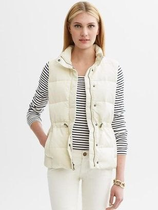 white down vest with striped T-shirt and skinny jeans
