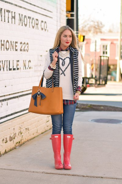 white embroidered sweater with blue jeans and orange knee-high rain boots