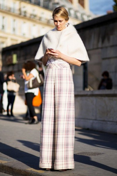 white faux fur cape with plaid palazzo trousers
