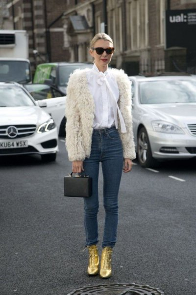 white faux fur jacket with a white bow tie and gold boots