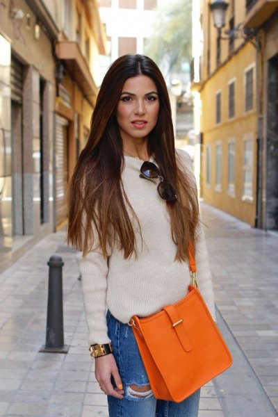 white, fitted sweater with a round neckline, blue boyfriend jeans and an orange handbag