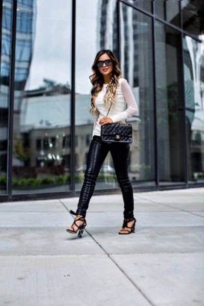 white fitted sweater with black leather lace-up trousers