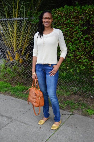 white, fitted sweater with blue skinny jeans and gold loafers with rounded toes