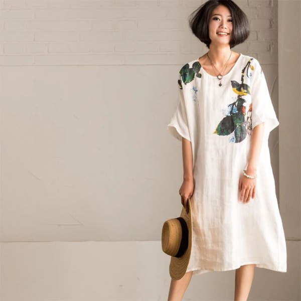 white swing dress made of linen with a floral pattern