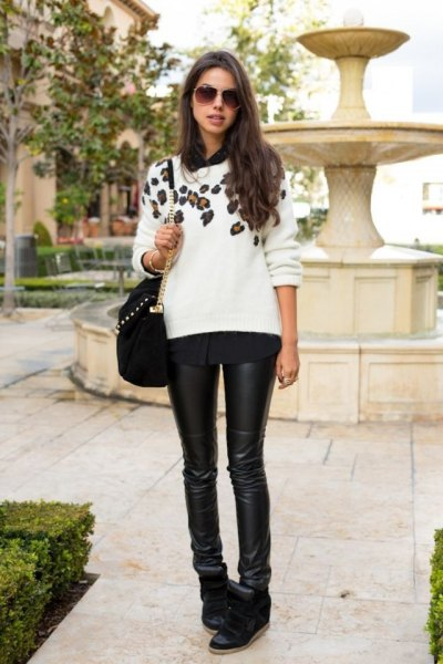 white sweater with floral pattern, black leather pants and wedge sneakers
