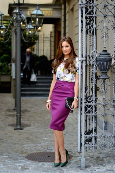 white, short-sleeved top with floral pattern and purple, high-waisted midi skirt