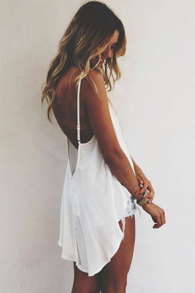 white flowing backless high-low tank top with denim shorts