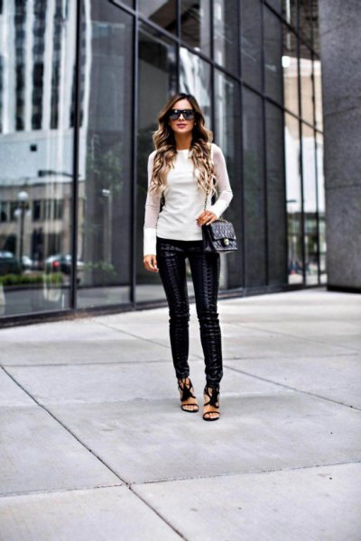 white, figure-hugging long-sleeved sweater with leather gaiters and open toe heels