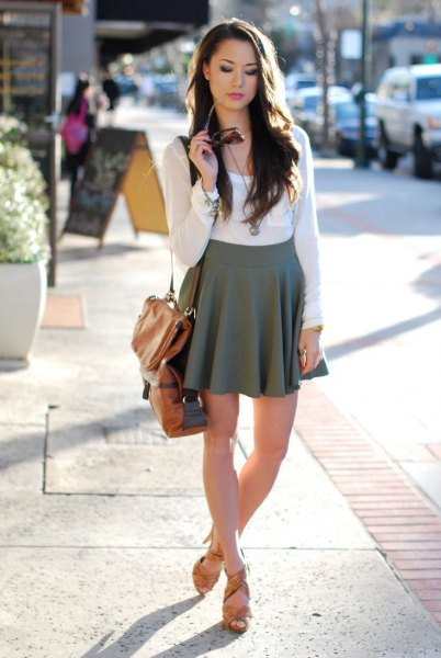 white, figure-hugging long-sleeved T-shirt with a gray, high-waisted minirater skirt