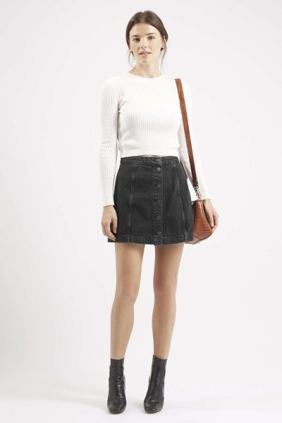 white, figure-hugging, ribbed sweater with black denim mini skirt with button placket