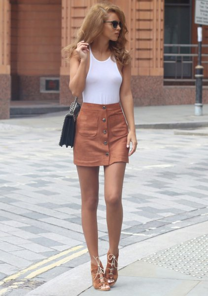white figure-hugging tank top with skyscraper skirt with camel button in front