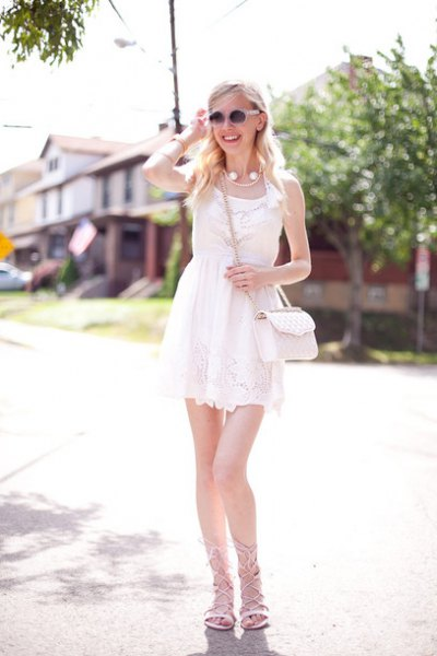 white mini lace dress with a gathered waist and gray, flat strappy sandals