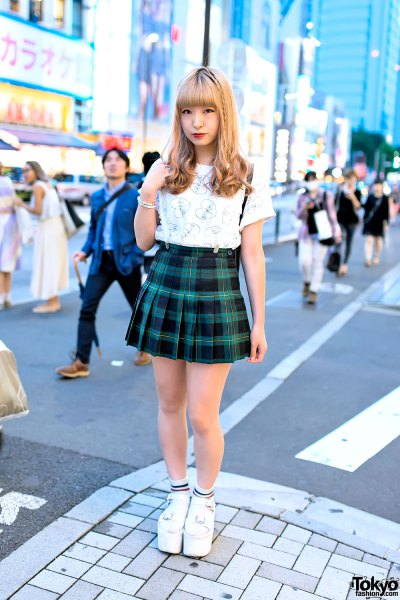 white graphic t-shirt with green and black checked mini pleated skirt