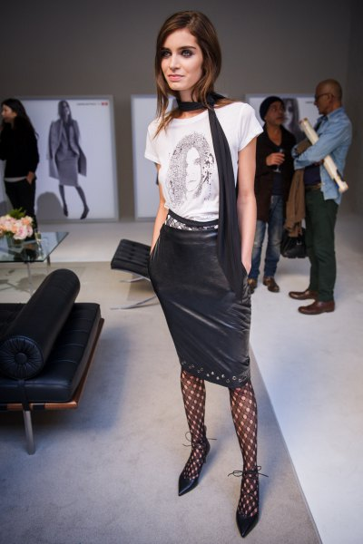 white graphic t-shirt with mini leather skirt and crossed tights