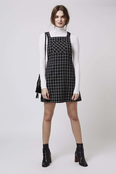 white high-necked sweater, black printed strap skater dress