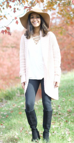 white cardigan with gray leggings and knee-high boots