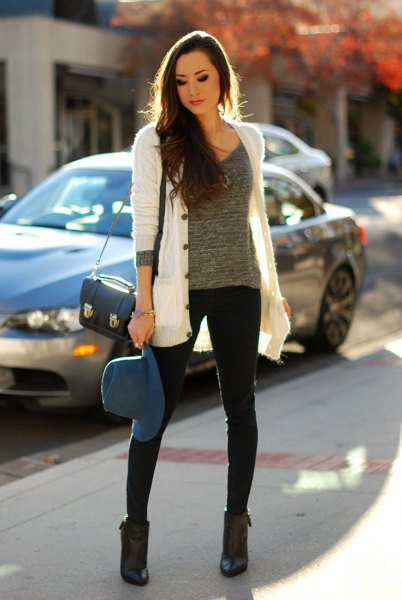 white cardigan with gray knitted sweater with scoop neckline and black skinny jeans
