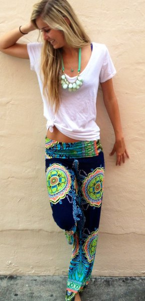 white knotted t-shirt with black and yellow beach pants with tribal print
