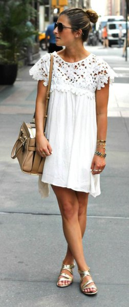 Pleated swing mini dress made of white lace with cap sleeves and golden strappy sandals