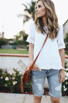white lace top with ripped long shorts made of gray denim