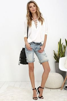 white long-sleeved blouse with a lace neckline and knee-length jeans shorts in light blue