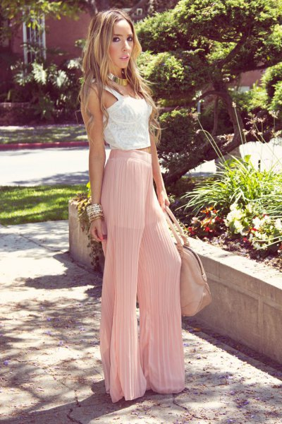 white lace vest above pink pleated pants