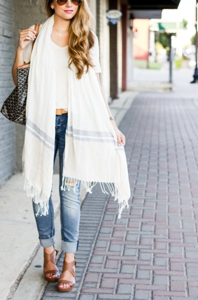 white long fringed scarf with white, short cut T-shirt and blue jeans with cuffs
